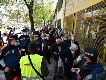 Votantes de las elecciones de Madrid esperan su turno para ejercer su derecho al voto en el Colegio Pinar del Rey en Madrid, este martes