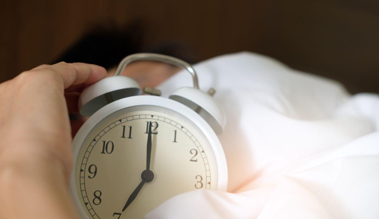 Una persona sujetando un reloj despertador mientras duerme