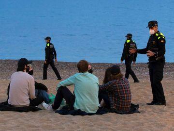 Varios policías patrullan por la playa de la Barceloneta, en Barcelona
