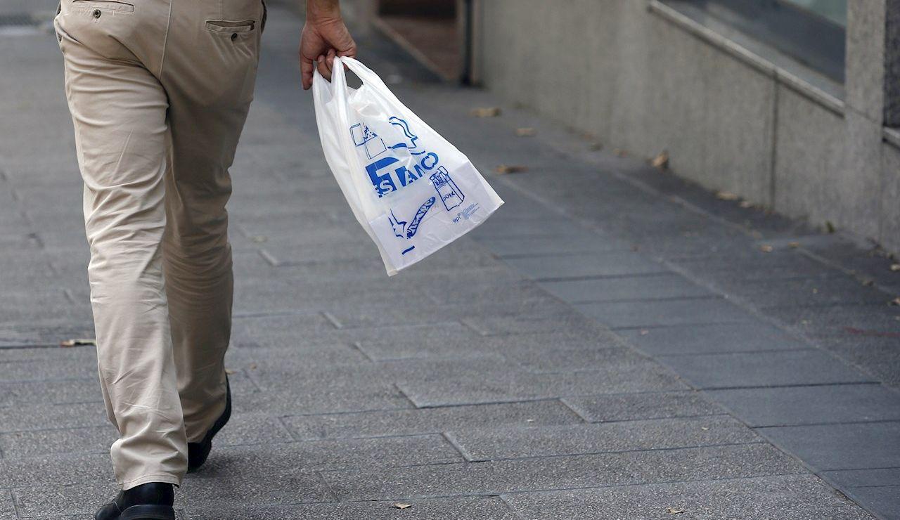 Un hombre camina por la calle portando una bolsa de plástico
