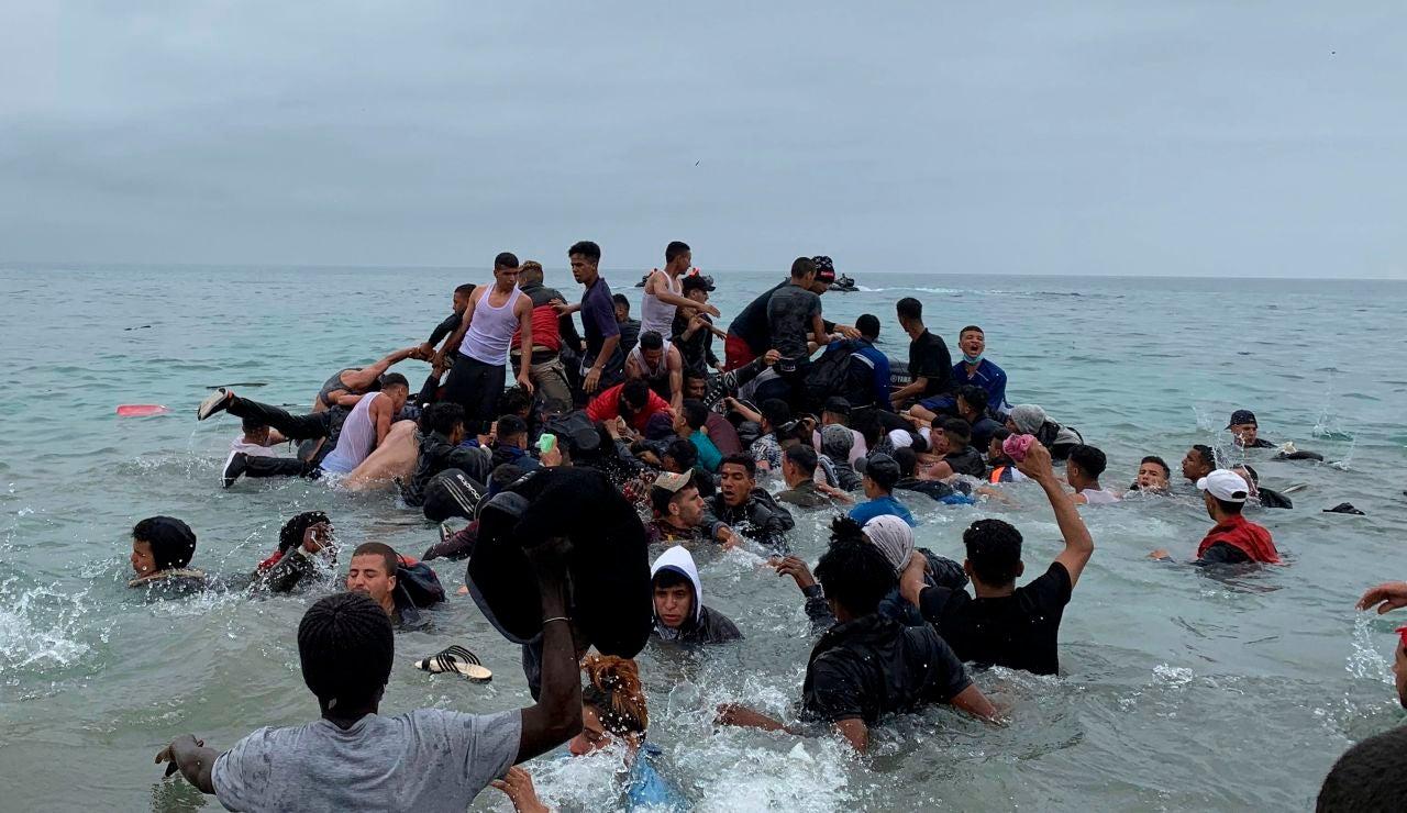Un grupo de personas se hacen con una embarcación de las autoridades marroquíes en la playa de la localidad de Fnideq (Castillejos)