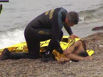 Un guardia civil auxilia a un inmigrante llegado a Ceuta