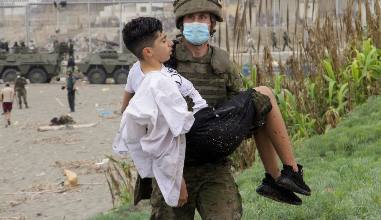 Un soldado del Ejército de Tierra ayuda a un inmigrante que ha logrado cruzar uno de los espigones fronterizos de Ceuta este martes en una avalancha de inmigrantes sin precedentes en España al registrarse la entrada en 24 horas de 5.000 personas (un tercio de ellas menores).