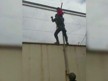 Un grupo de legionarios rescata a un menor en la valla del Tarajal