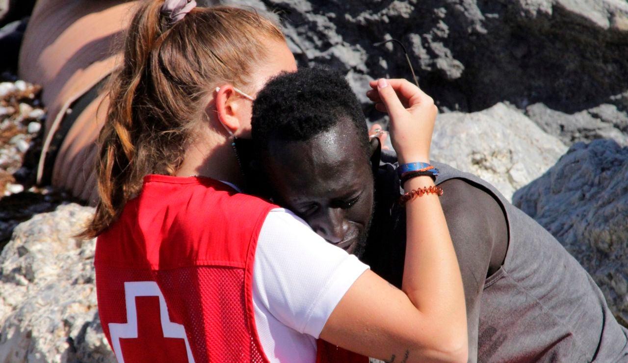 Voluntaria de Cruz Roja consuela a un migrante en Ceuta