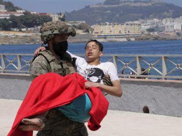 Un soldado traslada a un inmigrante en la playa fronteriza de El Tarajal de Ceuta