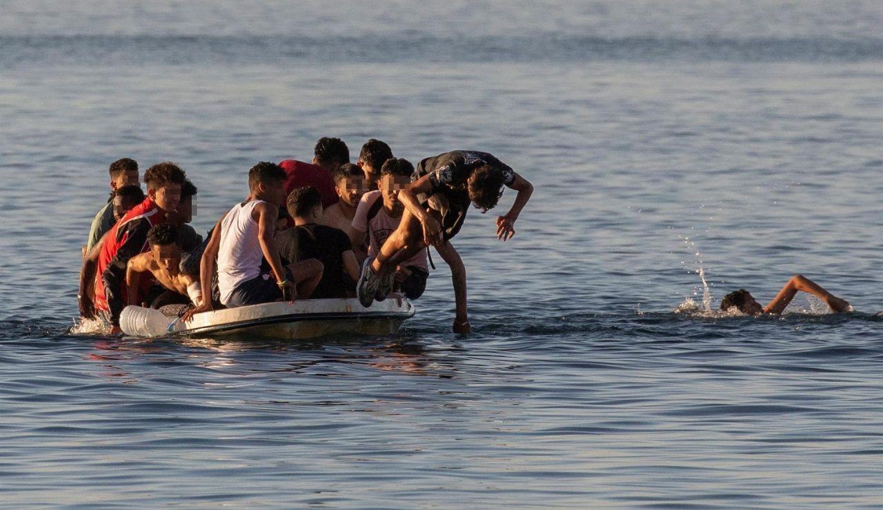 Varios menores migrantes se lanzan al agua para alcanzar la playa ceutí de El Tarajal mientras intentan llegar a España a bordo de una barca este miércoles.