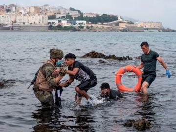 Un miembro del Ejército ayuda a menores migrantes llegados a Ceuta.