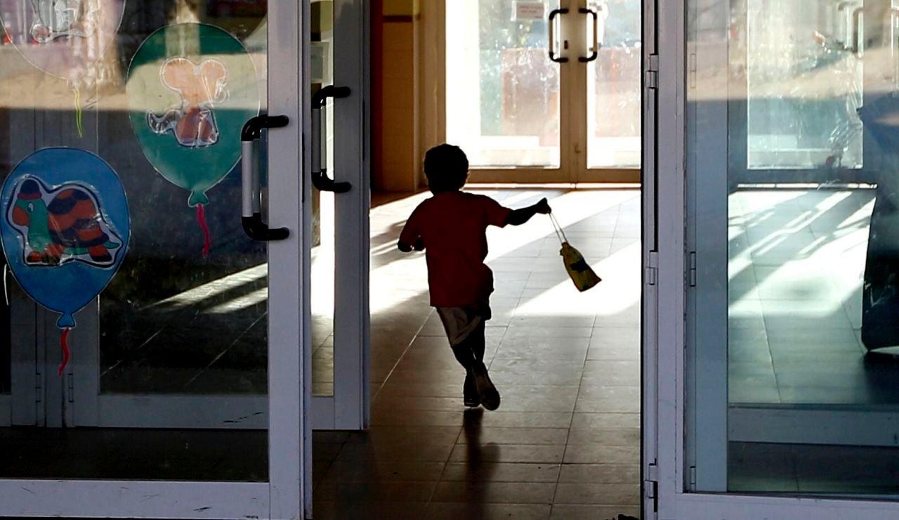 Un niño entrando al colegio corriendo