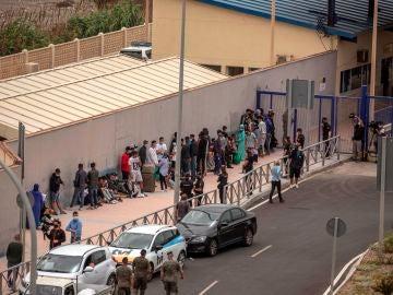 Varios migrantes esperan para pasar la frontera entre Ceuta y Marruecos