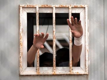 Dos menores sacan sus manos por una ventana del albergue de Piniers