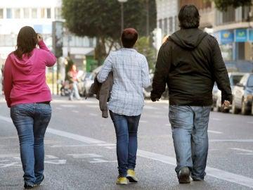res jóvenes pasean por una calle de Valencia