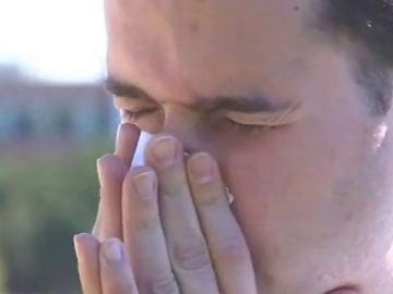 Un hombre estornuda por alergia