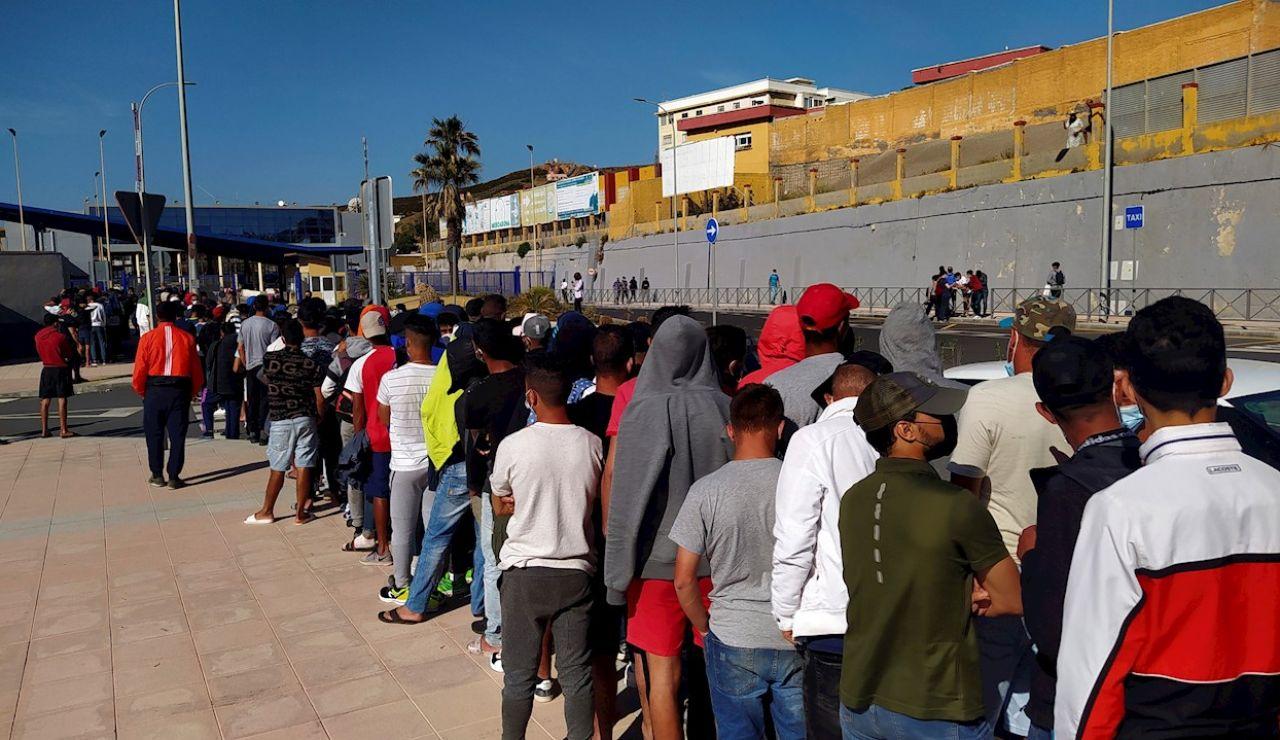 Inmigrantes marroquíes hacen cola desde primeras horas de la mañana de este miércoles, ante la oficina de Asilo y Refugio de la frontera del Tarajal en Ceuta