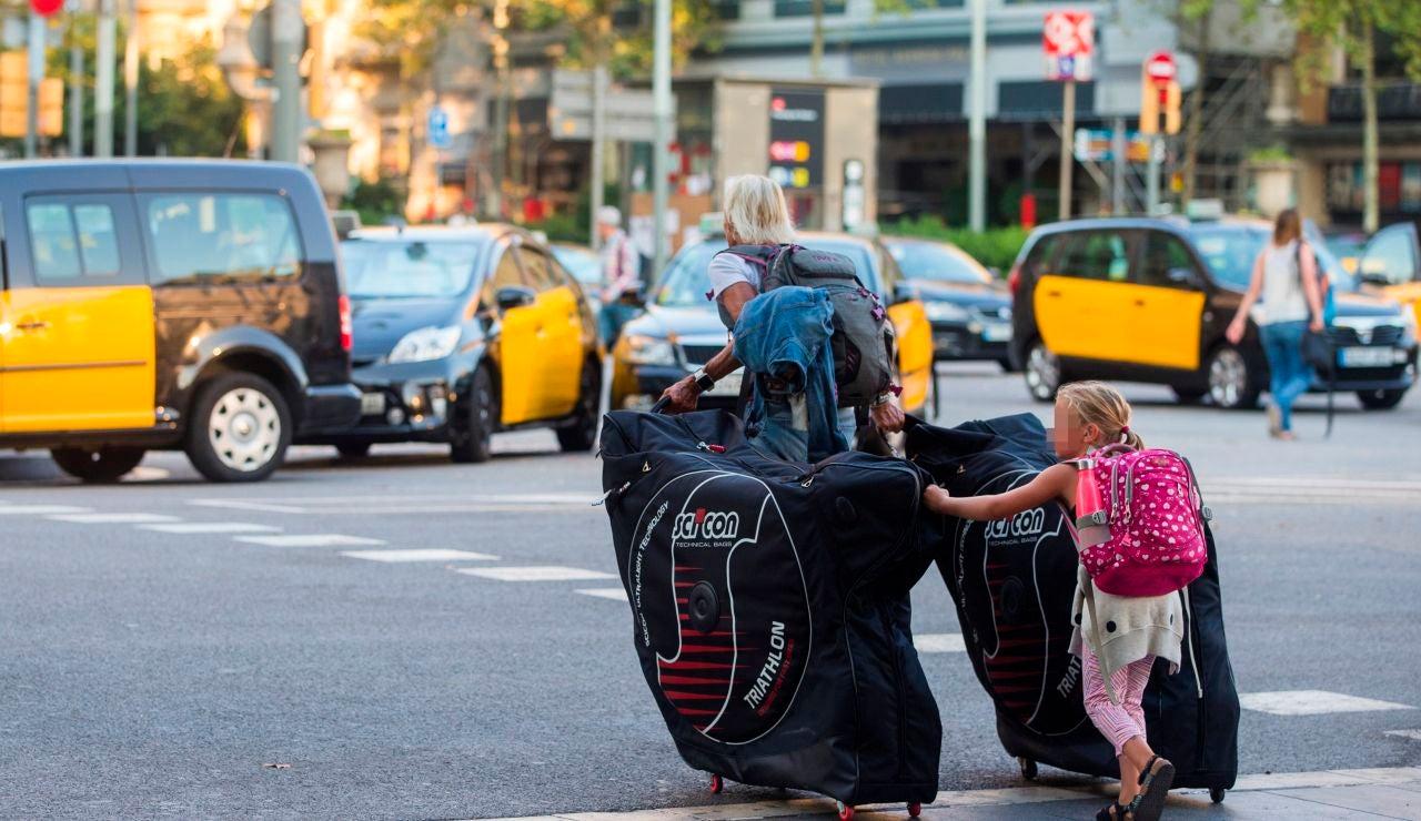 Unos turistas llevan sus maletas por las calles de Barcelona