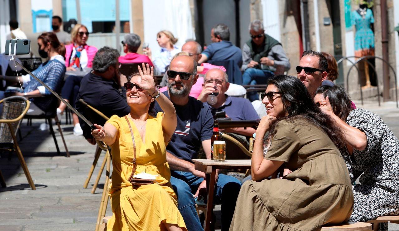 Unos turistas disfrutan en una terraza en Santiago de Compostela