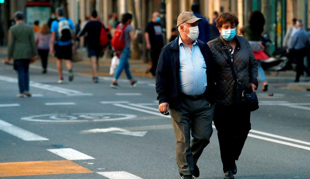 Una pareja pasea con mascarillas en Cataluña