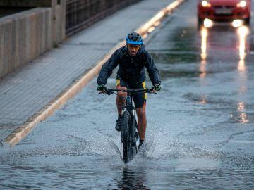 Un ciclista circula por una calle inundada en Ourense