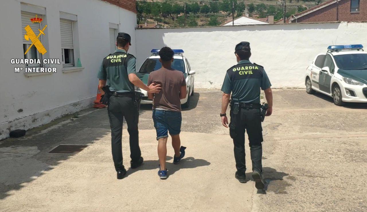 El joven siendo detenido por dos agentes.