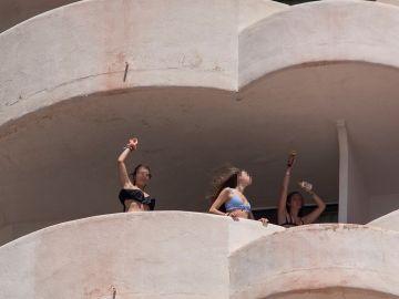 Tres jóvenes que se encuentran en aislamiento tras tener relación directa o indirecta con el brote por covid de un viaje de estudios en Mallorca, bailan en la terraza de una habitación del hotel