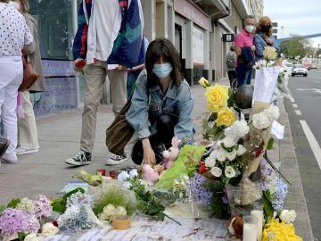Una mujer deposita el pasado martes flores en el lugar donde asesinaron a Samuel Luiz, el joven de 24 años que perdió la vida en la madrugada del sábado tras recibir una paliza