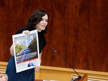 a presidenta de la Comunidad de Madrid, Isabel Díaz Ayuso, muestra una portada del ABC sobre la inconstitucionalidad del confinamiento declarado por el Gobierno nacional durante un pleno en la Asamblea de Madrid, este jueves