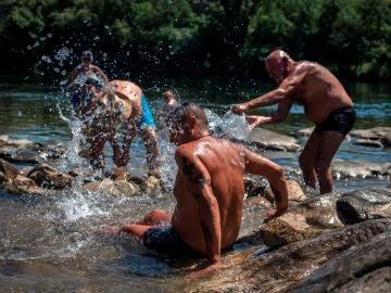 Varios hombres refrescándose por la ola de calor