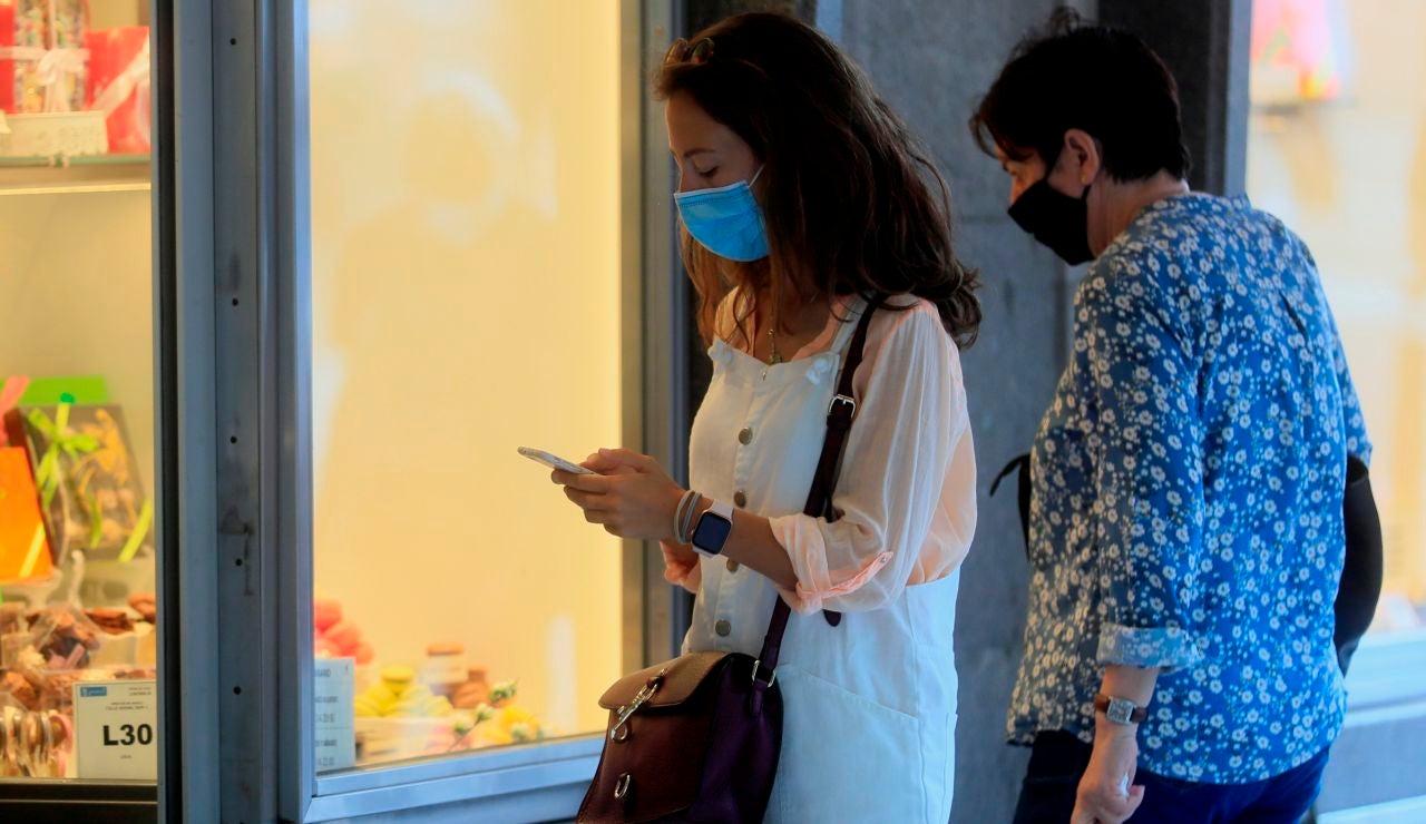 Dos personas con mascarillas, delante de un escaparate en Madrid