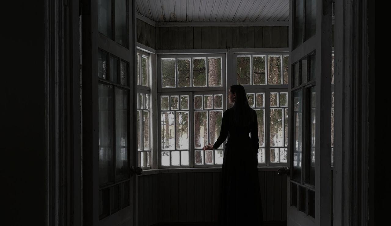 Una mujer mira por la ventana