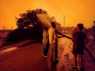 Varios habitantes de las isla griega de Evia luchan por apagar un fuego