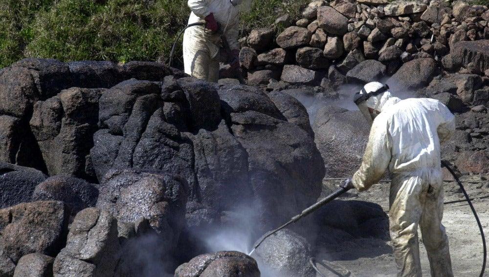 Unos operarios limpian la marea negra del Prestige