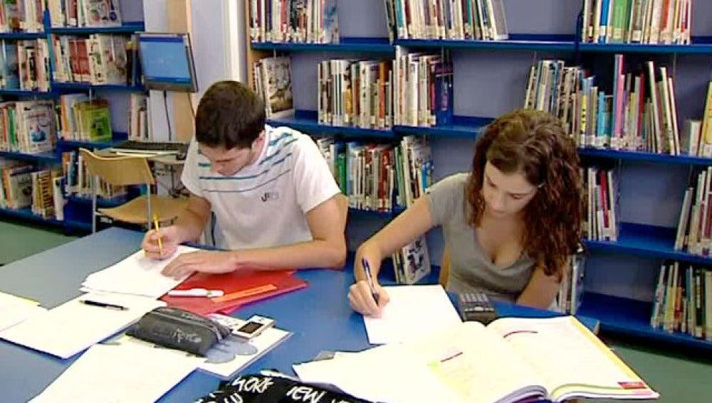 Dos jóvenes estudian en la biblioteca