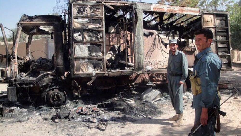 Policías afganos hacen guardia junto a un camión quemado