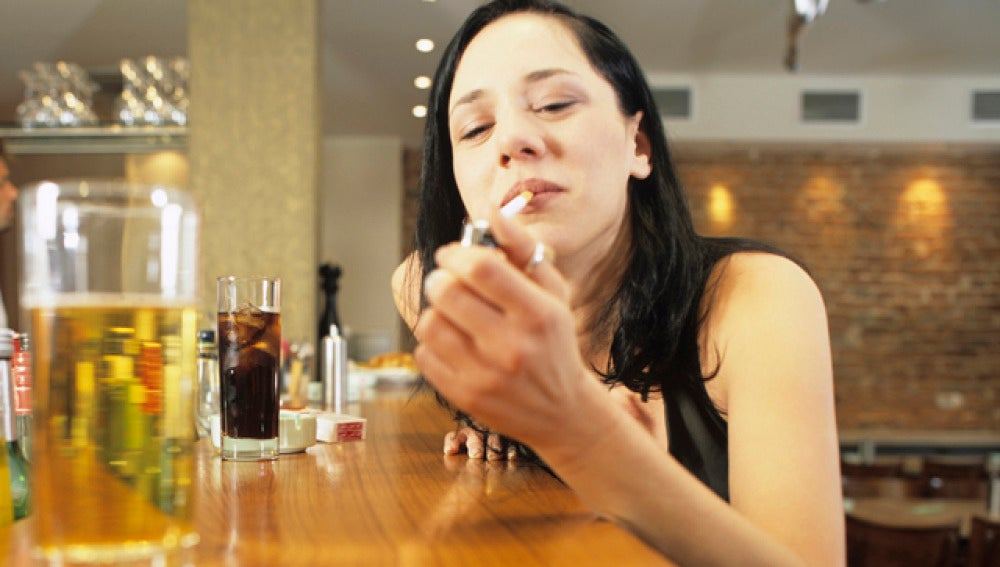 Una chica fuma en la barra de un bar