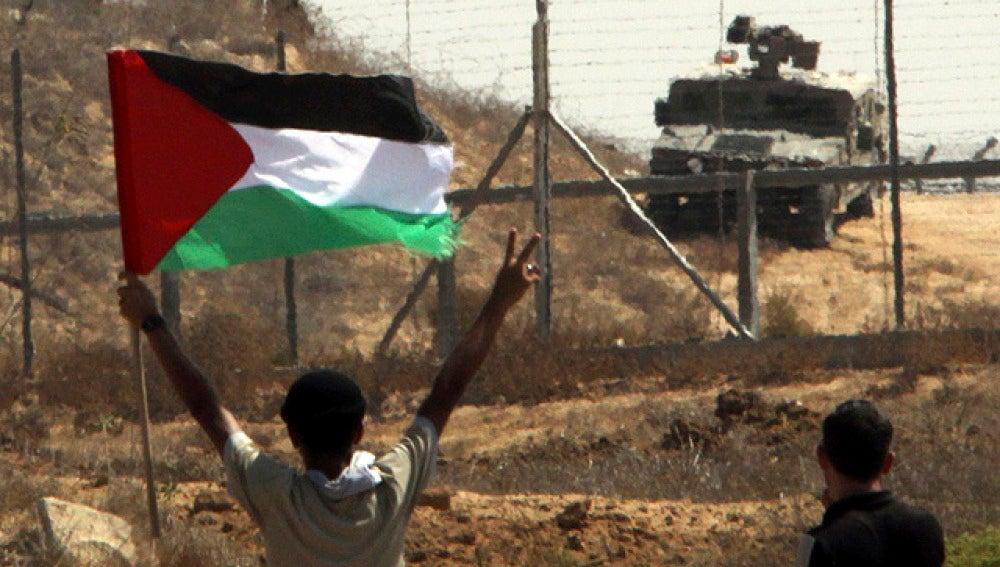 Ondea una bandera palestina ante las tropas israelíes