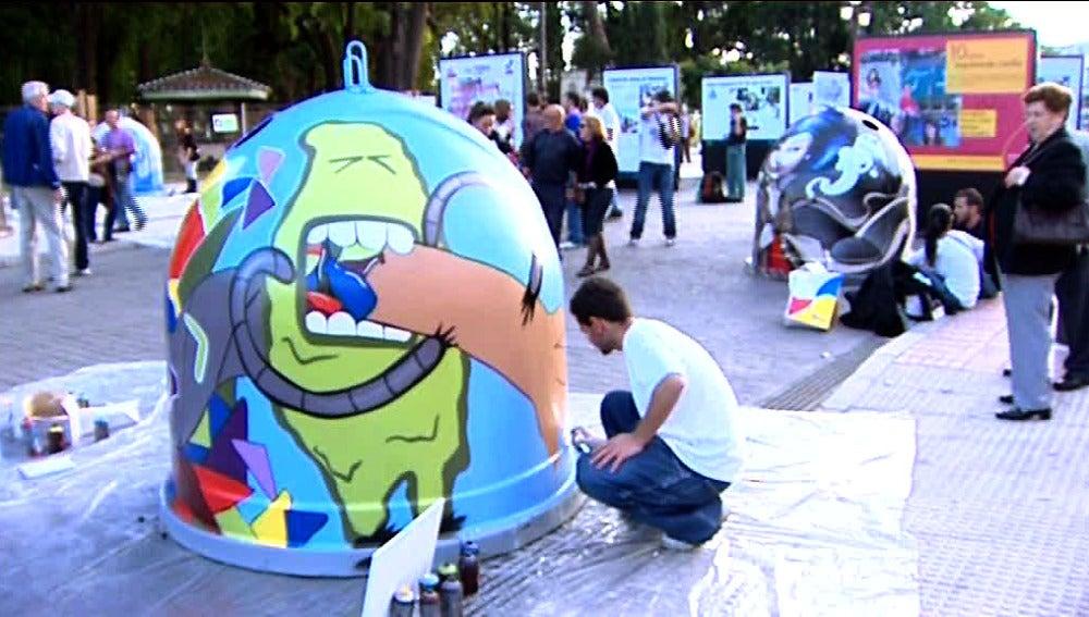 Un joven hace un graffiti en un contenedor