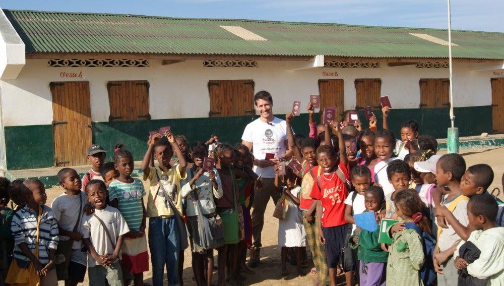 Jaime Cantizano entrega el pasaporte a los niños registrados.