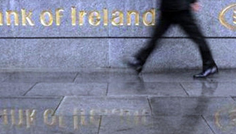 Un hombre pasa frente a la fachada del Banco de Irlanda