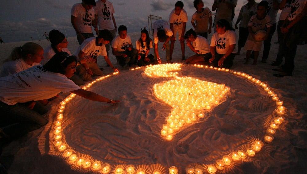 Dibujan Sudamérica con velas en la playa de Cancún