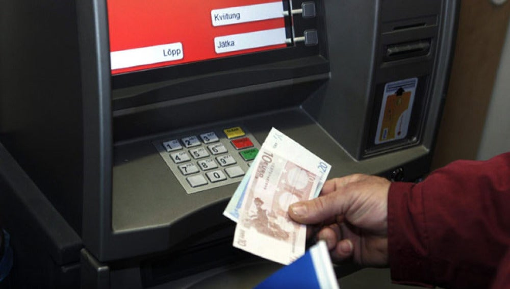 Un hombre saca billetes de euros en Tallín, Estonia