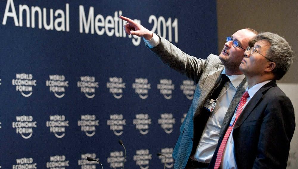 El ministro belga de Economía, Vincent Van Quickenborne, charla con el profesor de Economía Zhang Weiying