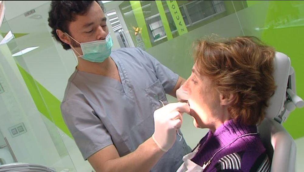 Un odontólogo atiende a un paciente