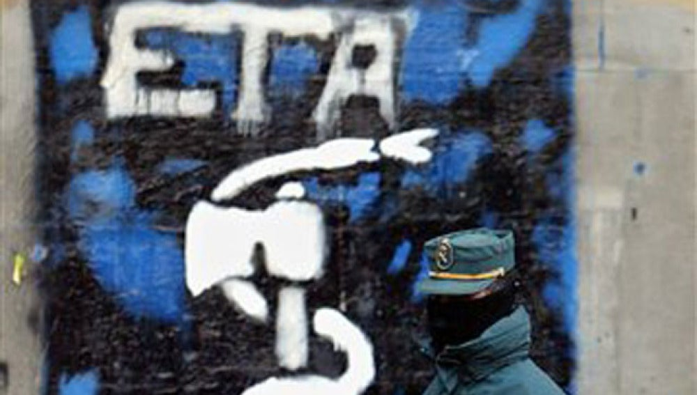 Un guardia civil delante de una pintada de ETA en el Pais Vasco