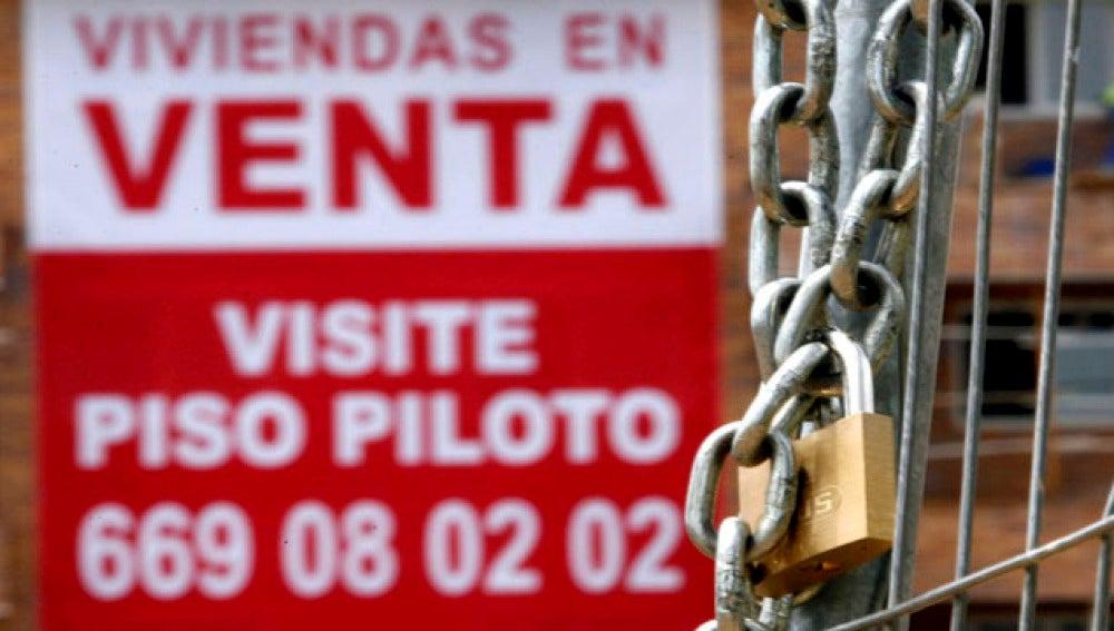 Un cartel anunciador de venta pisos cuelga de una fachada de una nueva promoción en Madrid.