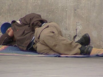 Un mendigo tumbado en la calle