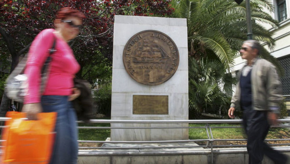 Varios viandantes frente a un monumento que hace honor a la antigua moneda griega
