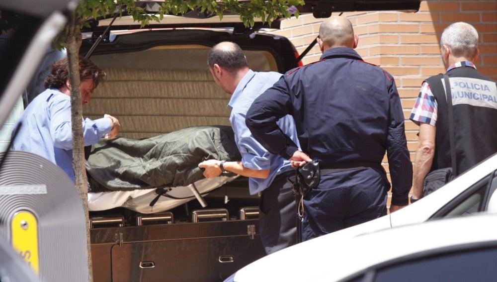 Empleados de la funeraria trasladan el cuerpo de la mujer y su hijo que han sido hallados muertos