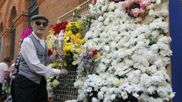 Un chulapo cuelga una flor en la ofrenda a la Virgen de la Paloma