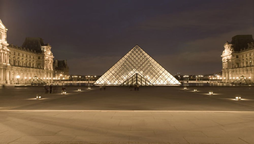 El parisino Museo Louvre iluminado en la noche de la ciudad.