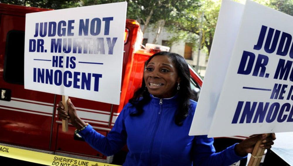 Una mujer sostiene carteles en las que anuncia que el doctor Conrad Murray es inocente.